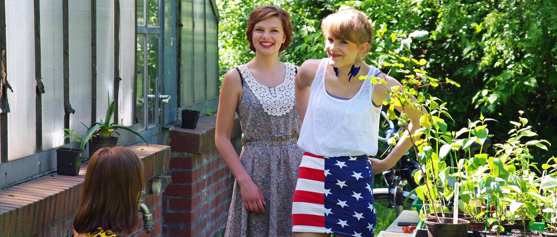 2 Frauen stehen vor dem Gewächshaus.