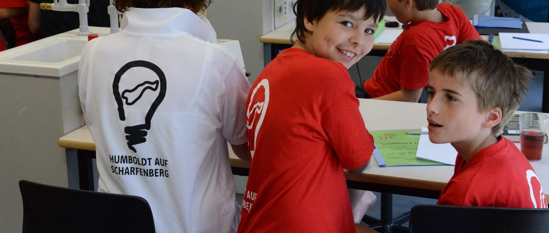 """3 Jungen sind im Chemie Raum. Sie tragen TShirts mit dem Schriftzug """"Humboldt auf Scharfenberg""""."""