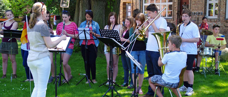 Schüler spielen Blasinstrumente auf der Wiese vor dem Fährhaus.