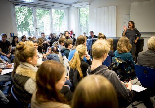 Viele Schüler sind in einem Raum und hören einer Frau zu.